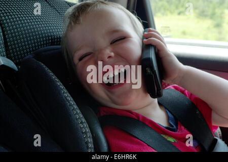 Un bébé dans un siège d'auto de rire faisant semblant d'utiliser un iphone