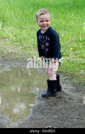 Un jeune garçon se tremper en marche dans une flaque d'eau Banque D'Images