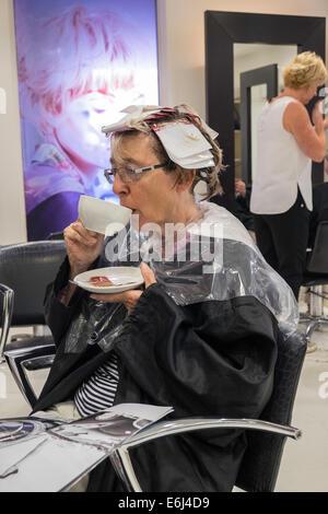 Femme PLUS ÂGÉE DANS UN SALON DE COIFFURE AYANT MIS EN FAITS SAILLANTS les cheveux tout en buvant du café. ENGLAND Banque D'Images