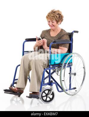 Belle femme senior handicapés à l'aide de smart phone sur fond blanc Banque D'Images