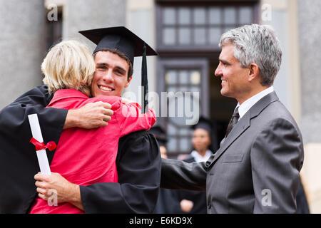 Professionnels diplômés masculins hugging sa mère à la cérémonie de remise des diplômes