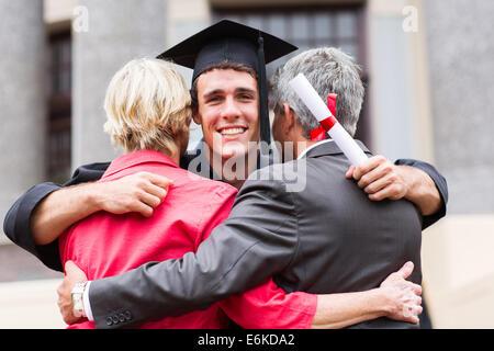 Beau jeune homme graduate serrant ses parents au moment de l'obtention du diplôme