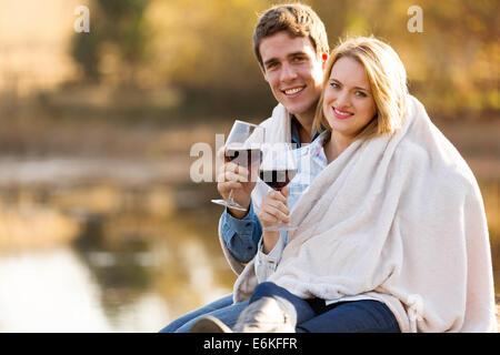 Beau jeune couple se blottir en plein air avec verre de vin