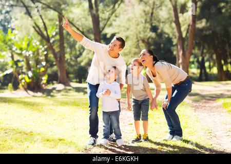 Heureux jeune famille l'observation des oiseaux en forêt Banque D'Images
