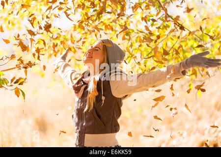 Les feuilles d'automne tombant sur happy young woman in forest Banque D'Images