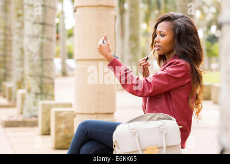 Belle femme africaine tenant un miroir et l'application de lustre de lèvre Banque D'Images