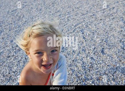 Portrait d'enfant blond girl laughing at pebbles beach background Banque D'Images