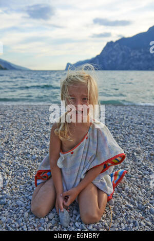 Portrait de jeune fille blonde enfant pleurer au fond de plage de galets Banque D'Images