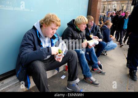 Londres, Angleterre, Royaume-Uni. Les jeunes gens assis à Trafalgar Square, manger Banque D'Images