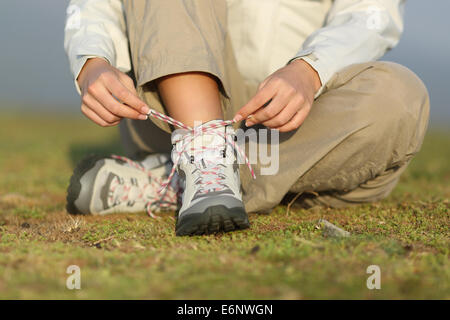 Attacher ses lacets de chaussures de randonnée femme bottes avec un arrière-plan flou