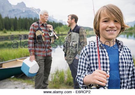 Trois générations d'hommes se tenant debout par still lake Banque D'Images