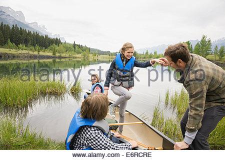 Père fille aidant à partir de canot dans le lac encore Banque D'Images