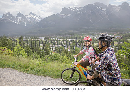Couple riding mountain bikes on hillside Banque D'Images