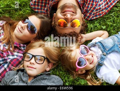 Papa et ses 3 filles se coucher sur l'herbe dans un style hippie lunettes heureux. Banque D'Images