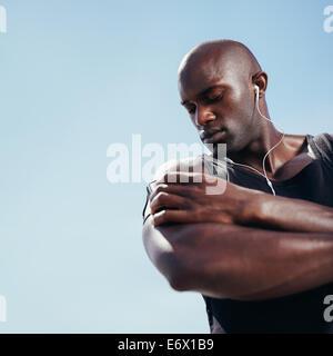 Low angle view homme musclé de l'Afrique de l'écoute de la musique sur téléphone mobile. Jeune homme fit contre Banque D'Images