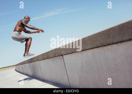 L'athlète africain torse nu sur la boîte de l'extérieur fit sauter sur un mur. L'homme musclé faisant fort saute Banque D'Images