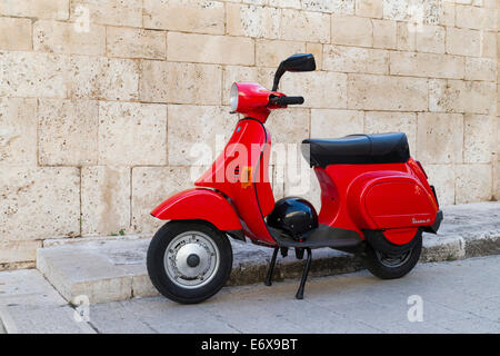 50 Vespa scooter avec casque rouge, garée devant un mur, Alberobello, Pouilles, Italie Banque D'Images