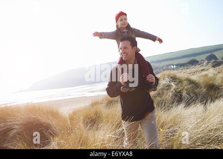 Père et fille marche à travers les dunes sur la plage d'hiver Banque D'Images