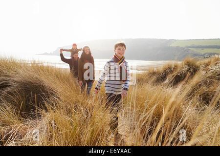 Balades en famille à travers les dunes de sable sur la plage d'hiver Banque D'Images