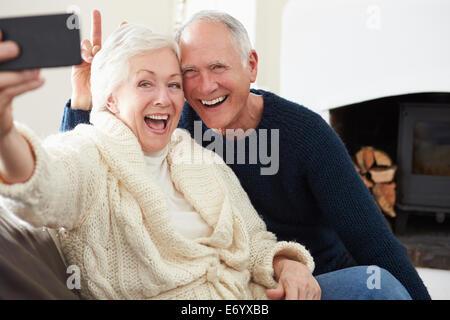 Senior Couple Sitting on Sofa prenant Selfies Banque D'Images