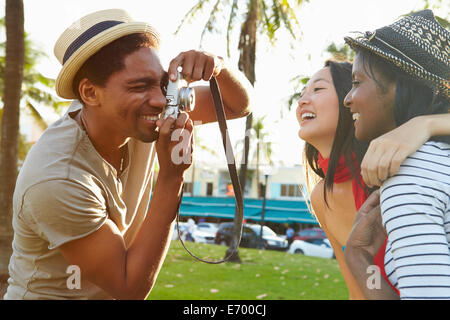 Man Taking Photograph des femmes dans Park Banque D'Images