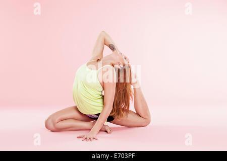 Studio shot of young woman in yoga position générale en arrière sur le plancher de toucher les orteils Banque D'Images