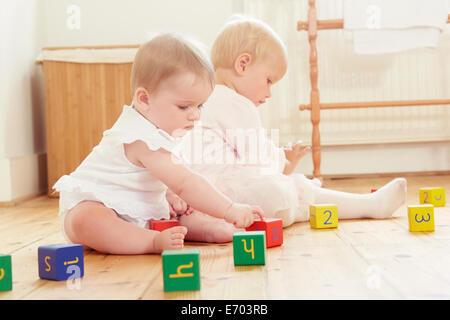 Sœurs bébé jouant sur étage avec blocs de construction Banque D'Images
