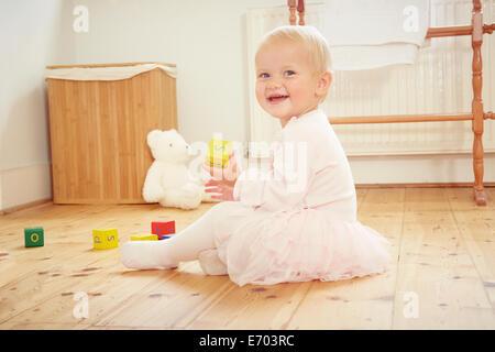 Portrait of smiling baby girl playing on étage avec blocs de construction Banque D'Images