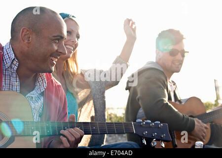 Trois amis adultes jouant guitare acoustique sur la plage de Bournemouth, Dorset, UK Banque D'Images