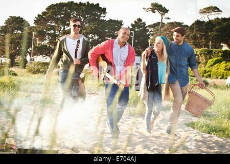 Quatre amis adultes avec guitare acoustique et panier pique-nique sur la plage de Bournemouth, Dorset, UK Banque D'Images