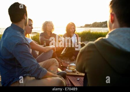 Cinq amis adultes avoir pique-nique sur la plage de Bournemouth, Dorset, UK