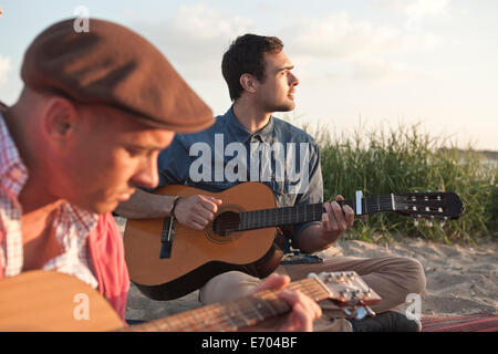 Deux mâles adultes amis jouant guitare acoustique sur la plage de Bournemouth, Dorset, UK Banque D'Images