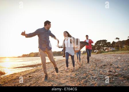 Groupe d'amis s'amusant sur la plage Banque D'Images