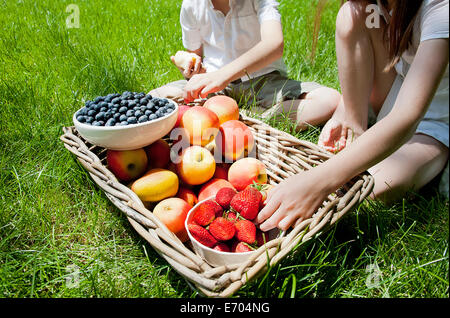 Portrait de frère et soeurs en mangeant des fruits de panier sur l'herbe Banque D'Images