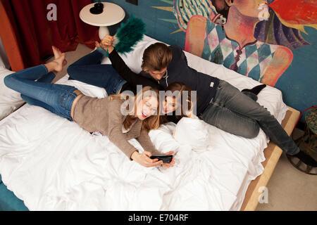 Trois amis adultes couché sur lit de l'hôtel prendre sur smartphone selfies Banque D'Images