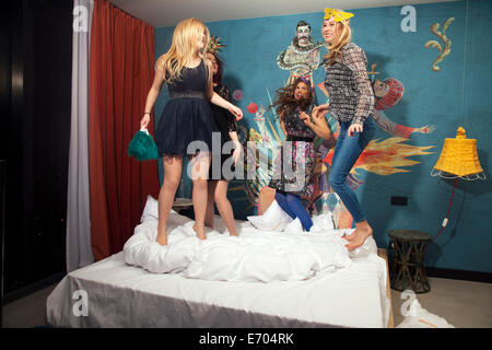 Quatre jeunes femmes friends dancing on hotel bed Banque D'Images