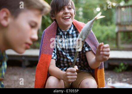 Young boy holding stick avec des poissons sur prêt à barbecue Banque D'Images