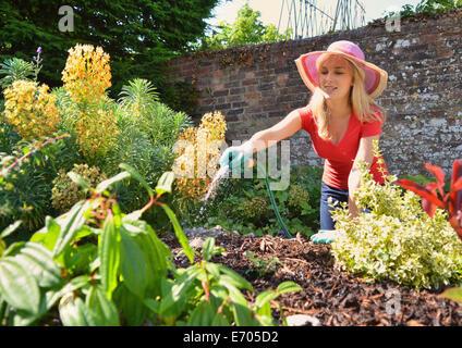 Jeune femme d'arrosage jardin avec arrosage Banque D'Images