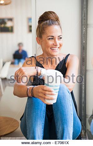 Mid adult woman sitting on window ledge de boire du café, à la fenêtre de Banque D'Images