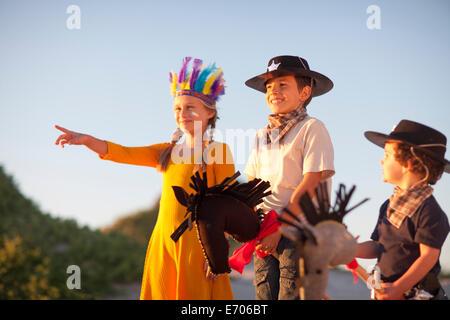 Trois enfants habillés comme des cow-boys et des amérindiens qui pointe de dunes de sable
