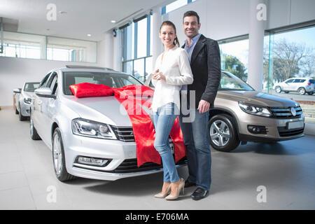 Portrait of mid adult couple et nouvelle voiture avec arc rouge dans l'agence de voiture Banque D'Images
