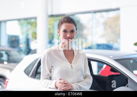 Portrait of smiling saleswoman in car dealership Banque D'Images