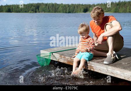 Père et fils assis sur la jetée du lac, Somerniemi, Finlande Banque D'Images