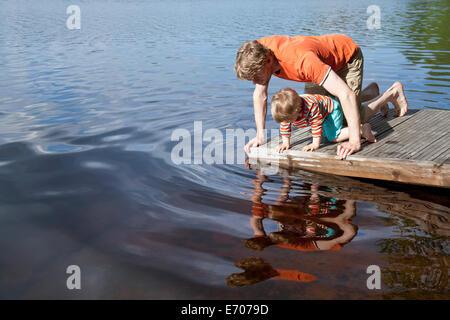 Père et fils à la recherche vers le bas dans le lac à partir de la jetée, Somerniemi, Finlande Banque D'Images