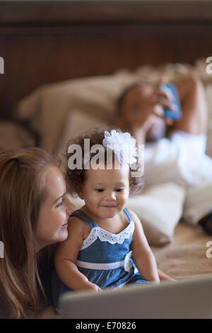 Bébé fille mère montrant un écran d'ordinateur portable Banque D'Images