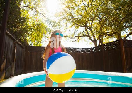 Girl holding beachball en bassin de jardin Banque D'Images
