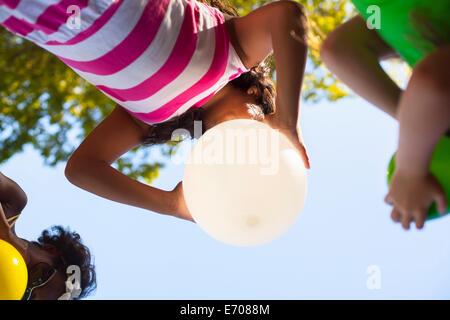 Portrait de trois filles du gonflage des ballons dans jardin Banque D'Images