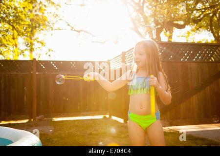 Girl Faire des bulles avec bubble wand dans jardin Banque D'Images
