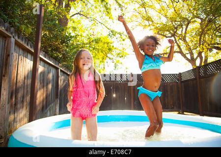 Deux jeunes filles sautant dans bassin de jardin Banque D'Images