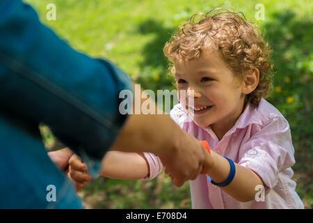 Jeune mère tenant son's hands in park Banque D'Images